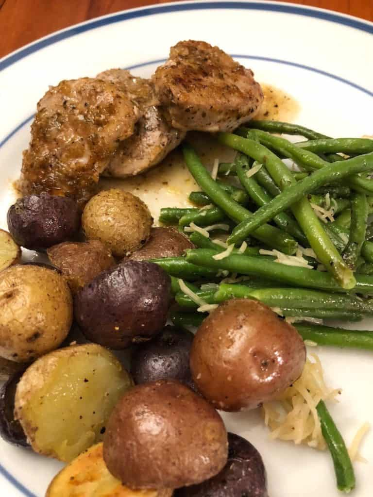 stove top pork tenderloin medallions with chili lime sauce on a plate with green beans and roasted potatoes.