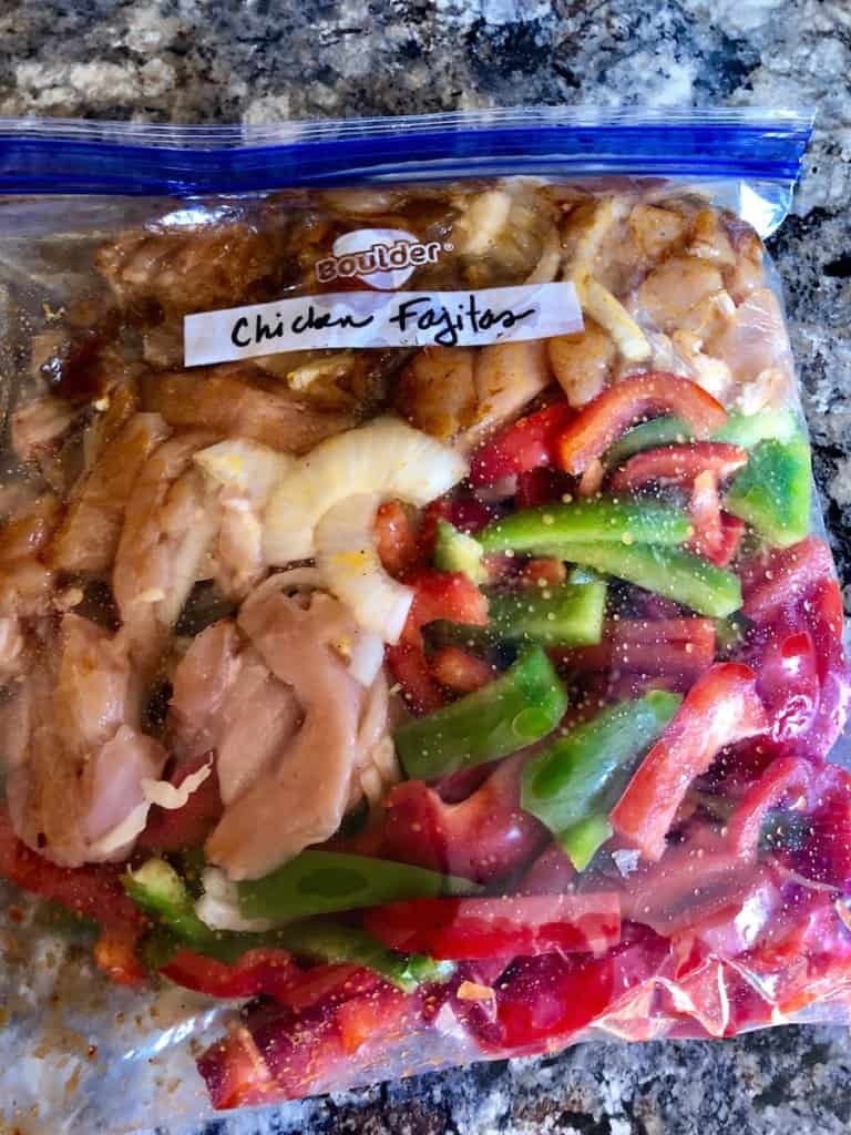 gallon sized zip lock bag filled with sliced chicken, seasoning, onions and peppers.